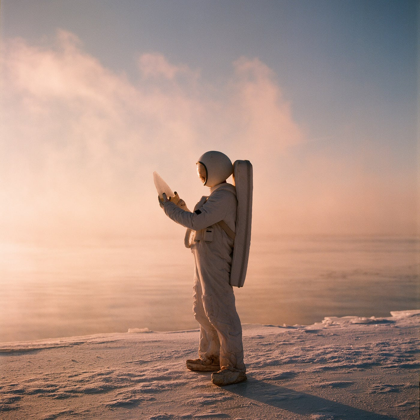 Side view of astronaut in costume standing among snowy plain and holding piece of ice.